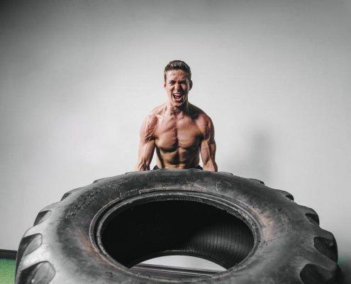 Man powerlifting tire